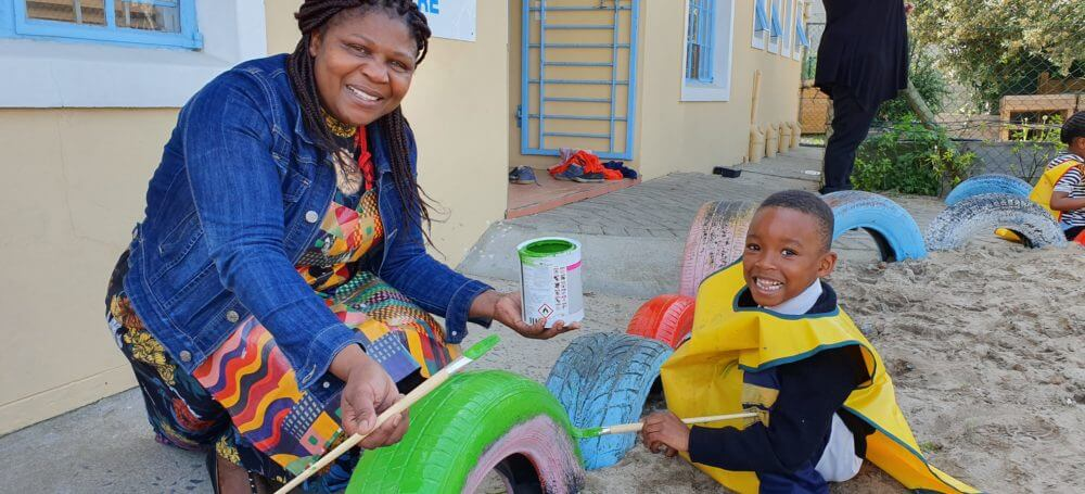 Thembeka Qubuda, principal of the pre-school doing some painting with the learners.